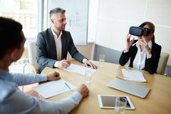 Two businessmen looking at their colleague wearing virtual reality headset Stock Photos
