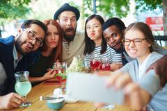 Group of freinds making funny faces for selfie Stock Photos