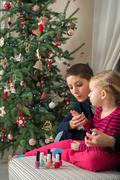Mother and daughter having fun painting finger nails on xmas day Stock Photos