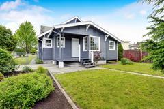 Backyard house exterior with siding trim, wooden floor porch and concrete wal Stock Photos