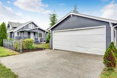 Separate garage exterior with siding trim, concrete driveway and white door.  Stock Photos