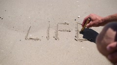 Wave washes the word life written on sand Stock Footage