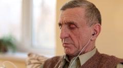 Senior man listens to music Stock Footage