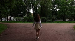 Young woman in short  skirt and white blouse go on gravel path and turn around Stock Footage