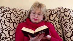 Woman sits on a divan and reads a book Stock Footage
