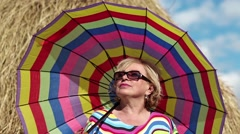 Blonde woman in sun glasses with many-coloured umbrella stands near haystack Stock Footage