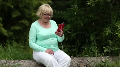 Woman sits on a fallen tree in the forest and communicates via his smartphone Stock Footage