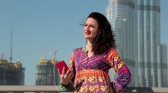 Brunette with red smartphone and earphones listens to music near skyscraper Stock Footage