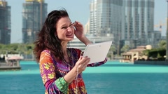 Woman stands near blue pool and skyscrapers and communicates via tablet pc Stock Footage