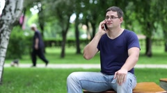 Adult man sits on the bench in city park and speaks on smartphone Stock Footage