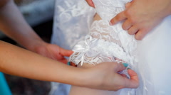 Bride dresses garter on the leg. Picture of beautiful female barefoot legs in Stock Footage