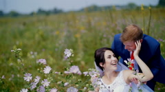 Newlyweds walking in a field - the bride and groom are playing with flowers Stock Footage
