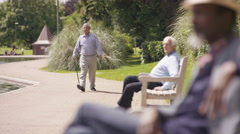 4K Senior man greeting a friend in the park & sitting down for a chat Stock Footage
