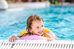 Girl lying in swimming pool. Summer heat and water Stock Photos