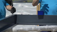 Two workers are winding screws into a big piece of material Stock Footage