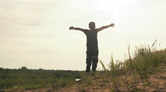 In the meadow boy spread his arms slow motion video Stock Footage