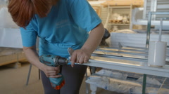 Woman is working with a drilling machine to adjust small items on a rod Stock Footage