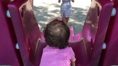 A happy baby girl going down a red slide and being caught by her mother, 4K Stock Footage