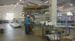 Worker in the factory is looking for some material on the table Stock Footage