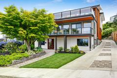 Modern three level house exterior with wooden trim and spacious two balconies Stock Photos