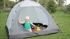 Beautiful baby is playing with a large tent on the grass. Baby less than a year - stock footage