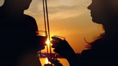 Young couple in love on sail boat with glasses of wine at sunset in slowmotion Stock Footage