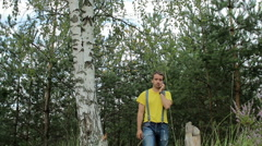 Man hiker walking through the forest and talking on the phone. Yellow T-shirt Stock Footage