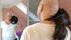 Unhappy woman ill with cancer is taking off her wig in front of a mirror Stock Footage