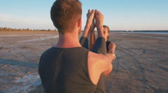 Two persons doing couple yoga nauka asana boat pose on the beach at sunset,dolly Stock Footage