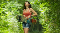 4K.Young girl  dance  with  skateboard in green park.Focus change Stock Footage