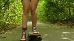 4K. Young beautiful  slendergirl  goes on  skateboard in summer park Stock Footage
