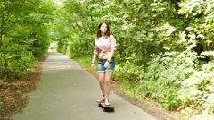 4K. Young beautiful   teenager girl  goes on  skateboard in summer park Stock Footage