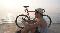 Young hipster man with his fixed gear bike using smart phone near the sea Stock Footage