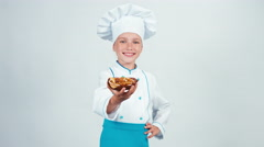 Close up portrait little chef cook holds in her hand cake with nuts and smiling Stock Footage