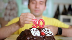 A man lights candles 30 years on a chocolate cake with butterfly wings. The man Stock Footage
