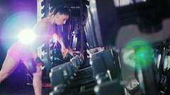 Motivation and commitment to the sport: athletic woman training in a hall in the Stock Footage