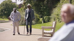 4K Senior man walking with friend in the park & sitting down to relax Stock Footage