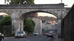 Cars going under arch of old bridge in Pau Stock Footage