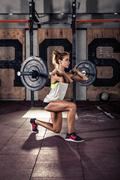 Sporty woman doing squat workout in gym Kuvituskuvat