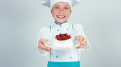 Little chef holds in hands biscuit cake sniffing and gives you Stock Footage
