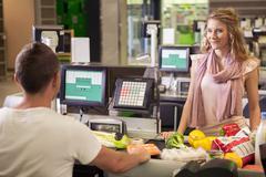 Woman buying food at supermarket Stock Photos