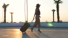 Young business lady walking with suitcase at the seafront during sunset Stock Footage