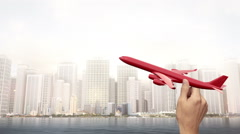 Hand Holding Commercial Airplane - City Scene Stock Footage