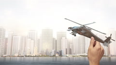 Hand Holding Attack Helicopter - City Scene Stock Footage