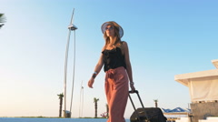 Young business lady walking with suitcase at the seafront Stock Footage