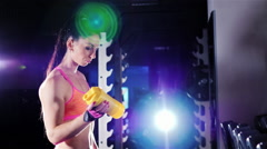 Athletic woman drinking a protein shake in a shaker in the gym. In the rays of Stock Footage