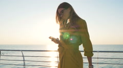 Young business lady with suitcase using smartphone at the seafront Stock Footage