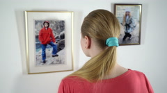 Framed photo prints hanging on the wall girl holding a photograph of little girl Stock Footage