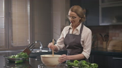 Beautiful housekeeper cooking in the kitchen.Shot on RED EPIC Cinema Camera. Stock Footage