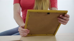 Teenage girl looking at the framed photo print in her hands Stock Footage